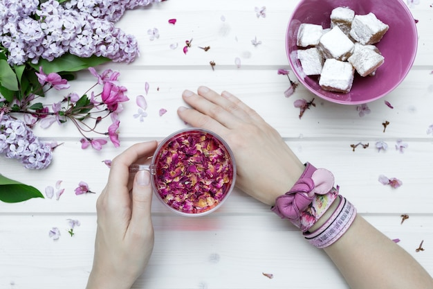 Pov ver uma pessoa com pulseiras rosa segurando um copo cheio de pétalas Foto gratuita