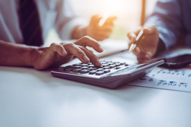 Povos asiáticos da idade média do negócio que usam a calculadora às contas de financiamento calculadoras. Foto Premium