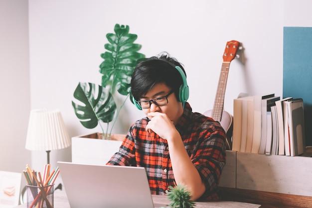 Povos asiáticos trabalhando no laptop e usando fone de ouvido estéreo para ouvir música enquanto trabalha em casa Foto Premium