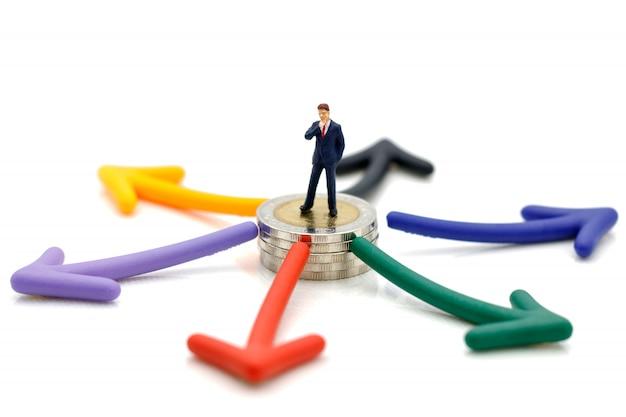 Povos diminutos que estão em moedas com escolha do caminho da seta. Foto Premium