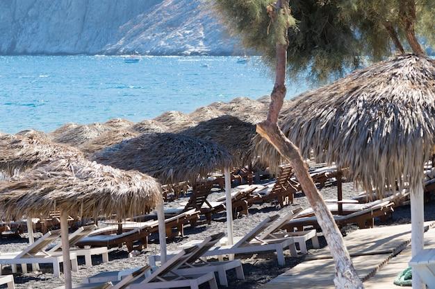 Praia com guarda-sóis e espreguiçadeiras em santorini Foto Premium