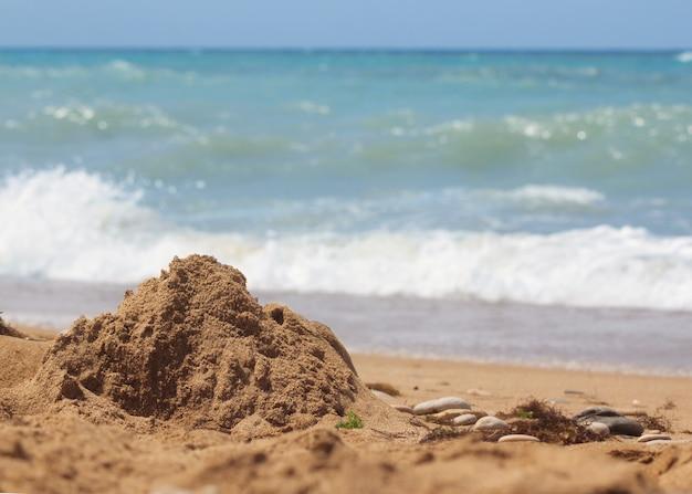 Praia de areia contra o céu azul e as ondas do mar, antes da tempestade que se aproxima. detalhe de água e areia. Foto Premium
