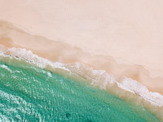 Praia de areia e linha de mar de cima Foto gratuita