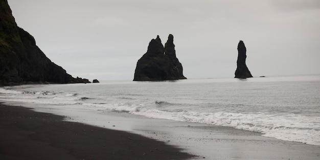 Praia de areia, falésias escarpadas no oceano Foto Premium
