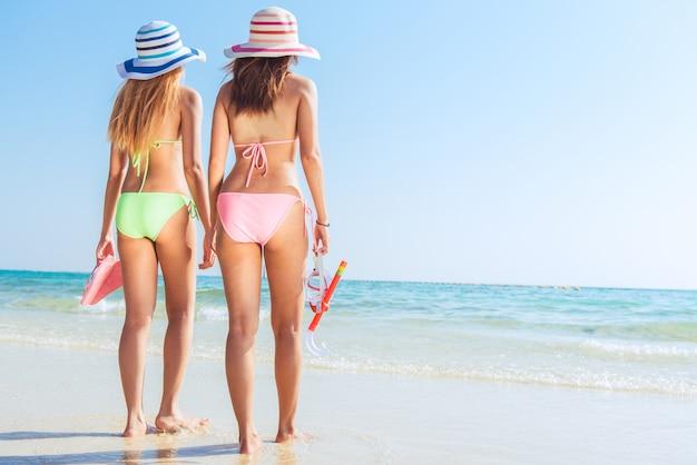 Praia de férias snorkel snorkeling com máscara e barbatanas. mulheres de biquíni que relaxam no refúgio tropical de verão fazendo atividades de snorkeling com tuba de mergulho e brilhos de nadadeiras. cuidados com o corpo da pele bronzeada. Foto gratuita