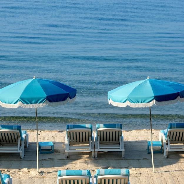 Praia do mediterrâneo com guarda-chuvas e cadeiras Foto gratuita