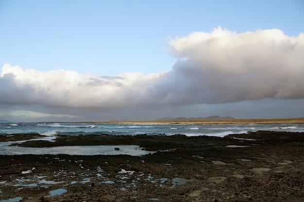 Praia rochosa e tempo nublado Foto gratuita