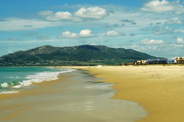 Praia rodeada pelo mar e montanhas sob o sol em tarifa, espanha Foto gratuita
