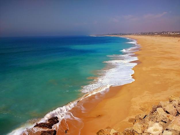 Praia rodeada pelo mar sob o sol em cádis, espanha Foto gratuita