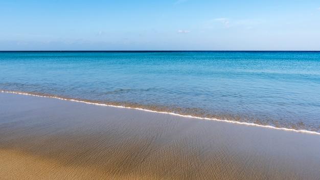 Praia tropical com céu azul e onda batendo na costa arenosa Foto Premium