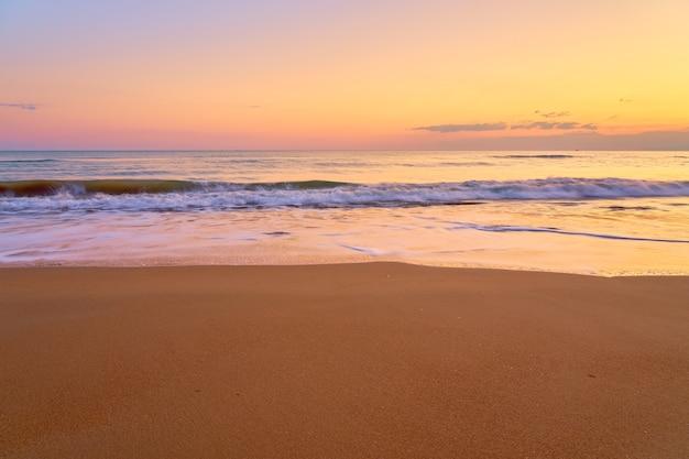 Praia tropical de areia ao pôr do sol Foto Premium