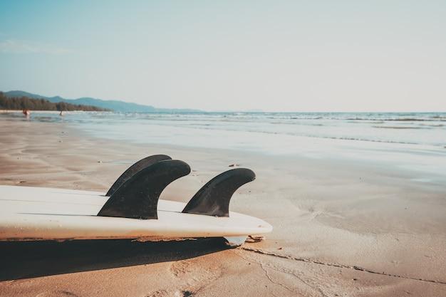 Prancha na praia tropical da areia com fundo calmo do mar e do céu do seascape. fundo das férias de verão e conceito do esporte de água. efeito de tom de cor vintage. Foto Premium