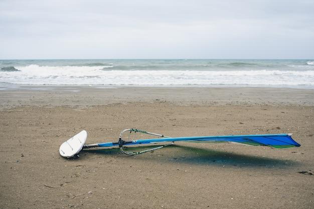 Pranchas de windsurf na areia de uma praia espanhola, enquanto os surfistas esperam pela onda certa. Foto Premium
