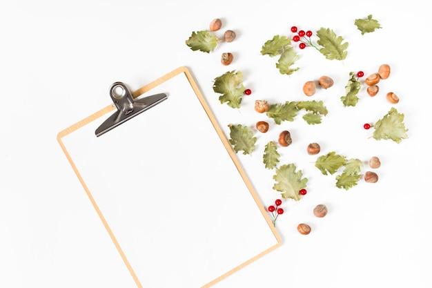 Prancheta com folhas e castanhas Foto gratuita