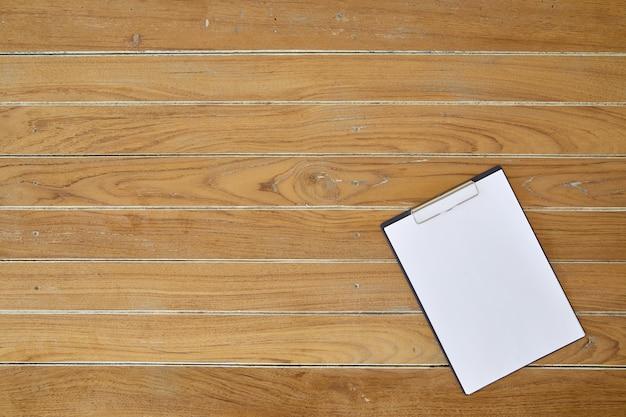Prancheta com lençol branco sobre fundo de madeira Foto Premium