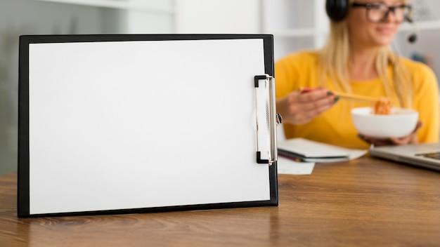 Prancheta de close-up na mesa com uma mulher atrás Foto gratuita