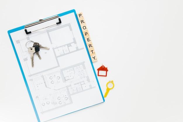 Prancheta do blueprint; chave de casa e bloco de propriedade com pano de fundo branco copyspace Foto gratuita
