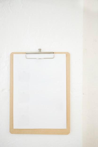 Prancheta em branco na parede branca. Foto gratuita