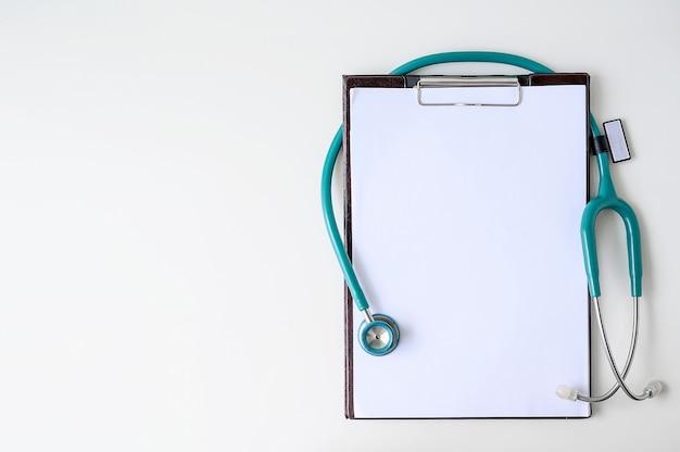 Prancheta médica em branco com estetoscópio Foto Premium