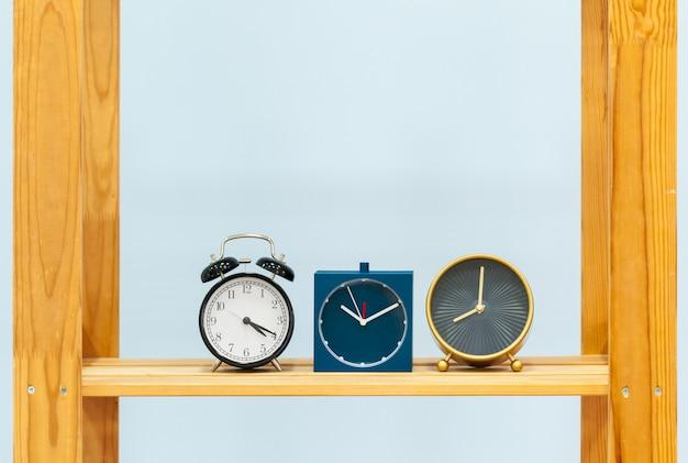 Prateleira de madeira com despertador e objetos contra o fundo azul Foto Premium