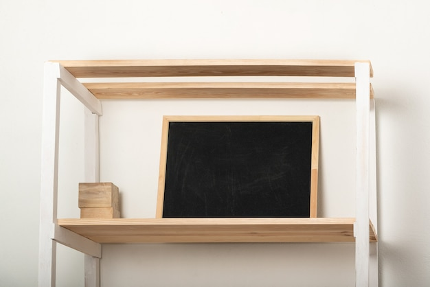 Prateleira de madeira e quadro de giz sobre fundo claro. interior em tons pastel. copie o espaço Foto Premium