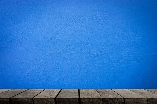 Prateleiras de madeira vazias com parede de cimento azul para exposição do produto Foto Premium