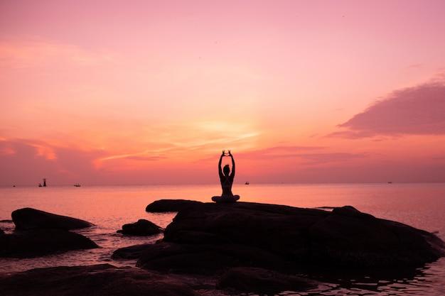 Prática de garota asiática yoga na praia dia de manhã do nascer do sol Foto Premium