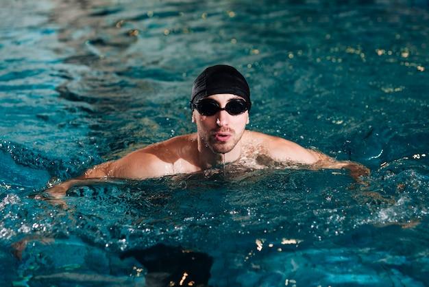 Prática de nadador masculino de ângulo alto na bacia Foto gratuita
