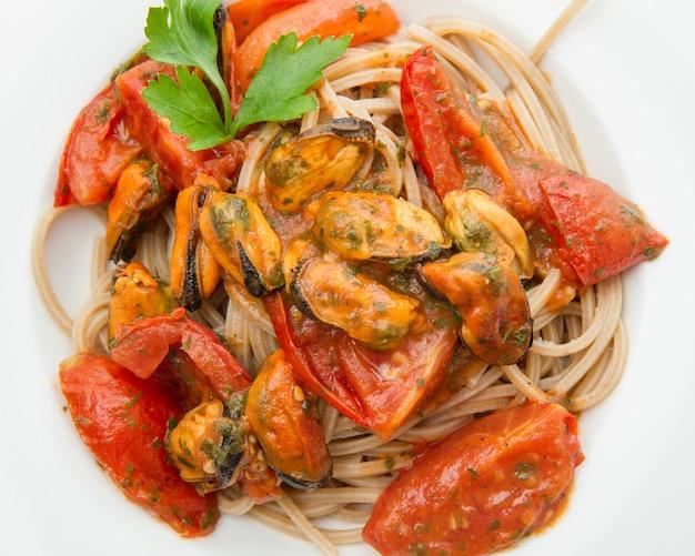 Prato branco com macarrão espaguete, mexilhão e tomate Foto Premium