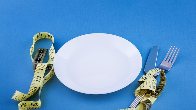 Prato branco vazio com fita métrica amarela amarrada. conceito de perda de peso. close-up de talheres. Foto gratuita
