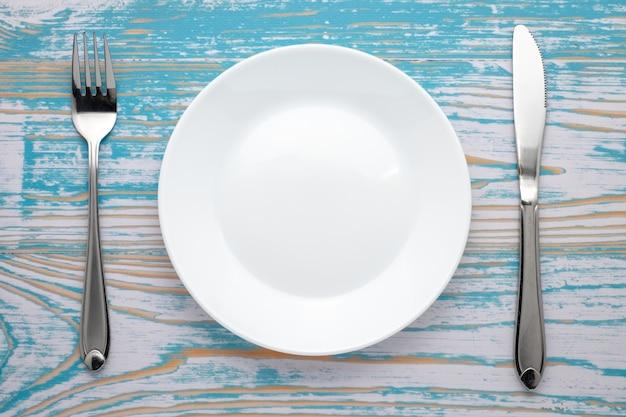 Prato branco vazio com prateado garfo e faca na mesa de madeira azul. ajuste de lugar do jantar. vista do topo. Foto Premium