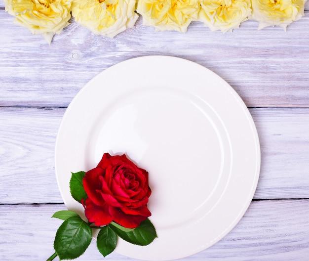 Prato branco vazio com uma rosa vermelha Foto Premium