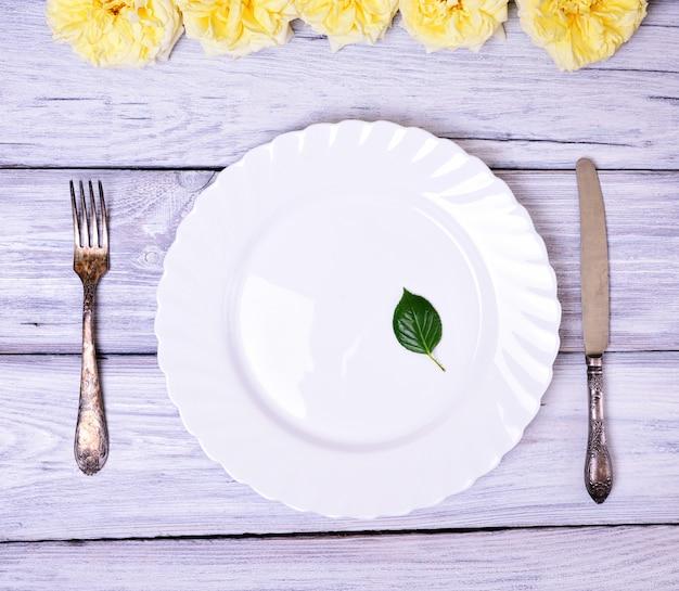 Prato branco vazio e garfo e faca de metal Foto Premium