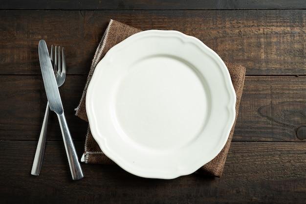 Prato branco vazio na mesa de madeira. Foto gratuita