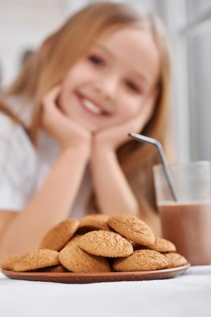 Prato com biscoitos e copo de leite com chocolate perto de menina Foto Premium