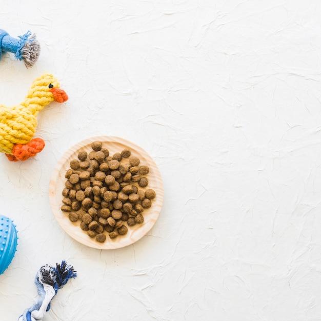 Prato com comida perto de brinquedos para animais de estimação Foto gratuita