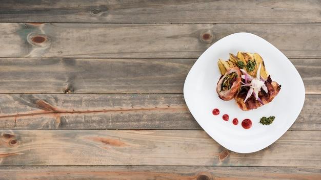 Prato com fatias de frango e batata rolo na mesa de madeira Foto gratuita