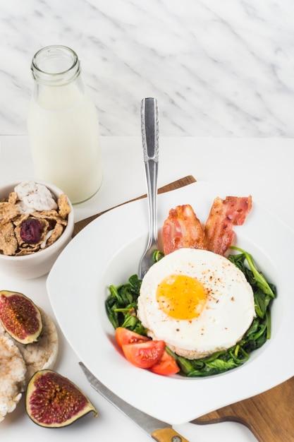 Prato com ovo frito com espinafre; bacon e tomate no fundo branco Foto gratuita