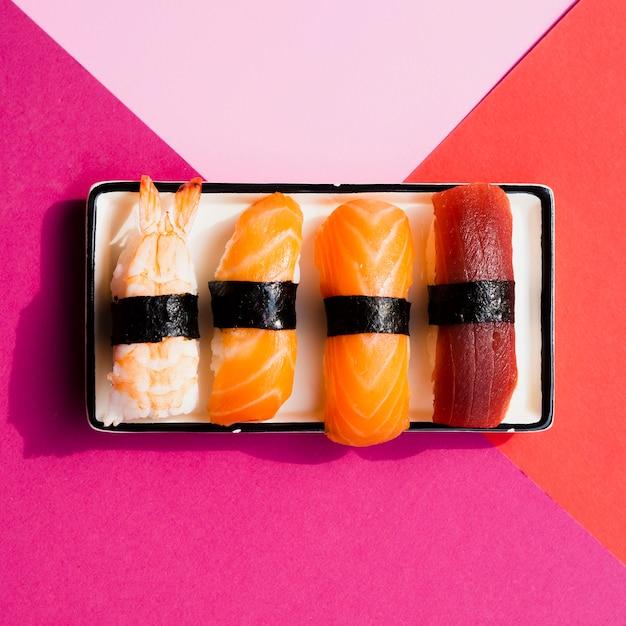 Prato com sushi em um fundo rosa e vermelho Foto gratuita