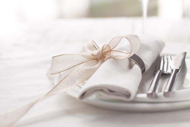 Prato com talheres bem decorados com guardanapo amarrado com uma curva dourada Foto gratuita