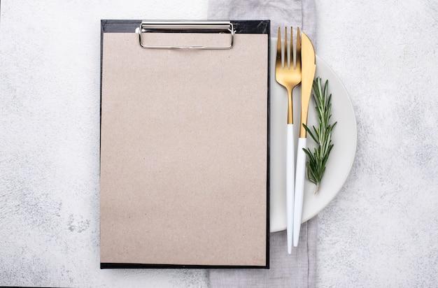 Prato com talheres e prancheta Foto gratuita