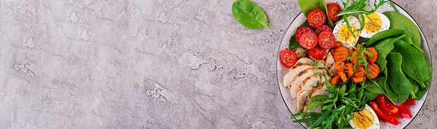 Prato com um alimento de dieta ceto. tomate cereja, peito de frango, ovos, cenoura, salada com rúcula e espinafre. keto almoço. vista do topo Foto gratuita
