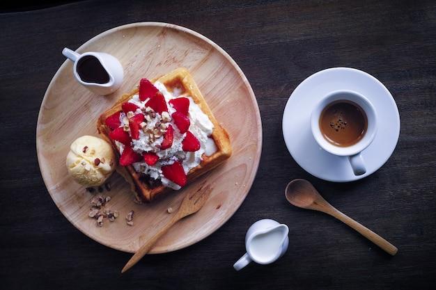 Prato com um brinde com creme e morangos e um café Foto gratuita