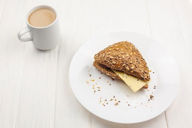 Prato com um sanduíche e uma xícara de café Foto gratuita