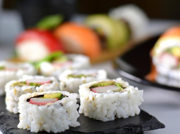 Prato com vários tipos de sushi, alguns de atum rabilho e outros salmões Foto Premium