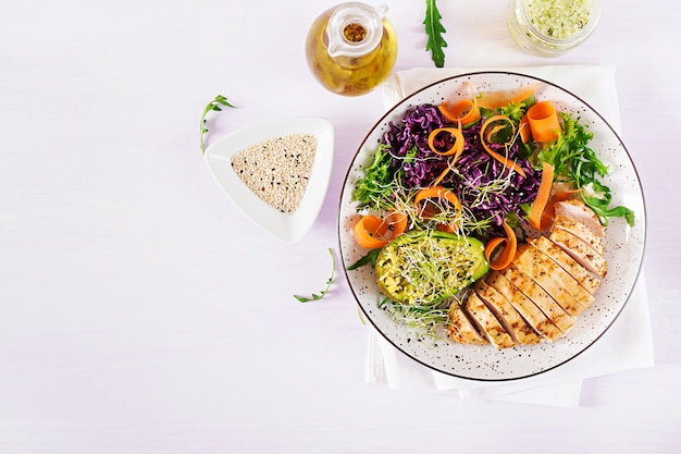 Prato da bacia de buddha com faixa da galinha, abacate, repolho vermelho, cenoura, salada fresca da alface e sésamo. Foto Premium