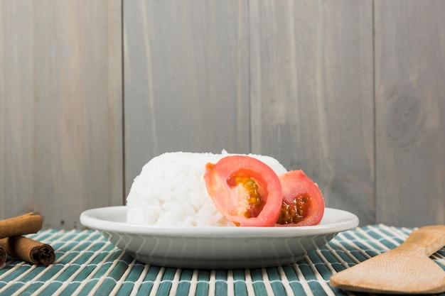 Prato de arroz com fatia de tomate; paus de canela e espátula de madeira em placemat Foto gratuita