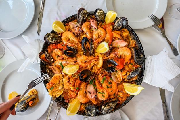Prato de arroz de paella de frutos do mar espanhol com camarão fresco, camarão, mexilhões, lulas, polvo e vieiras servido na panela. o garçom coloca uma porção no prato. vista do topo. restaurante Foto Premium