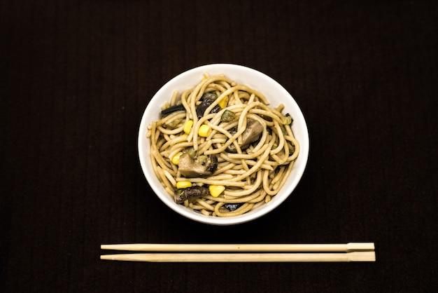 Prato, de, asiático, noddles, em, um, redondo branco, tigela, com, chopsticks Foto Premium
