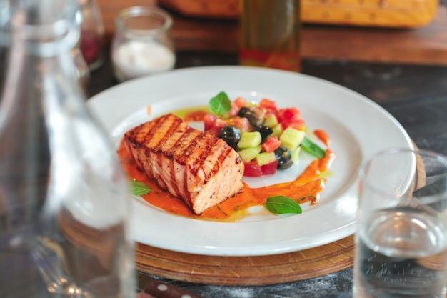 Prato de bife de salmão grelhado com legumes na mesa de madeira Foto Premium